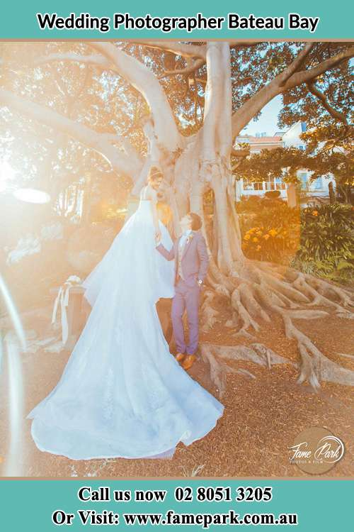 The Groom and the Bride hold their hands while looking at each other under the tree Bateau Bay