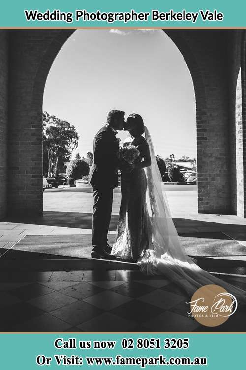 Photo of the Groom and the Bride kissing at the front of the church Berkeley Vale NSW 2261
