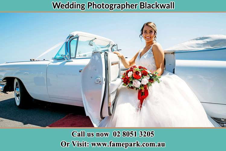 The Bride holding bouquet of flowers besides her bridal car Blackwall