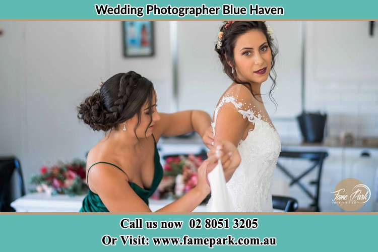 The Bride is being helped by bridesmaid trying to put her bridal gown Blue Haven