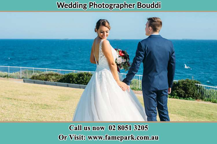 Photo of the Bride looking at her back as the Groom hold her hands Bouddi