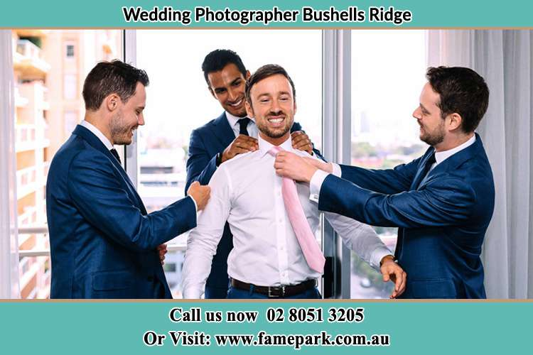 Photo of the Groom helping by the groomsmen getting ready Bushells Ridge NSW 2259