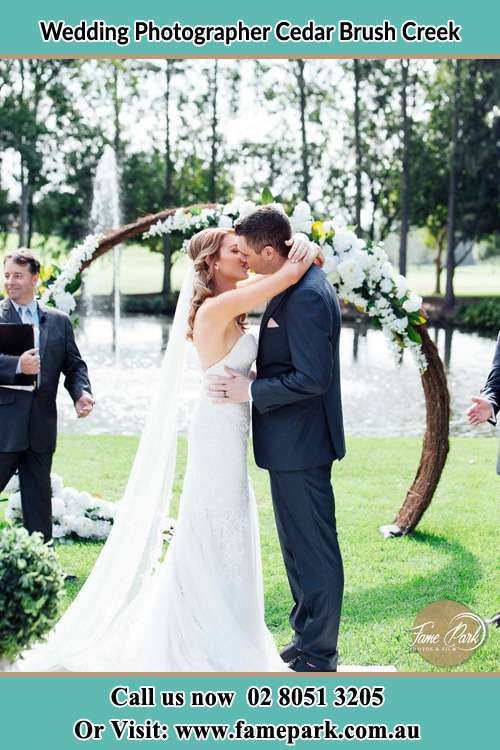 Photo of the Bride and the Groom kiss at the wedding ceremony Cedar Brush Creek