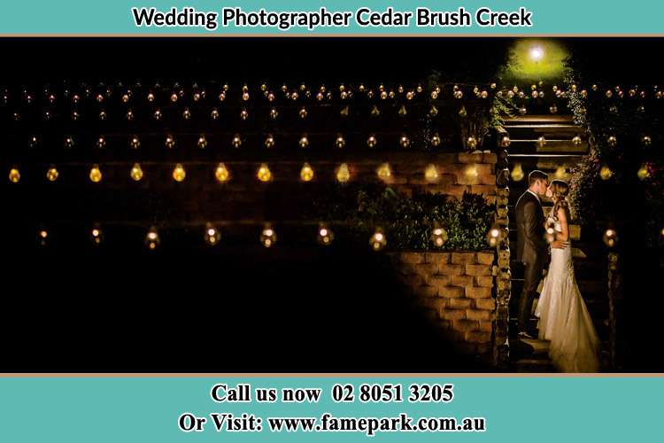 Photo of the new couple kissing at night Cedar Brush Creek