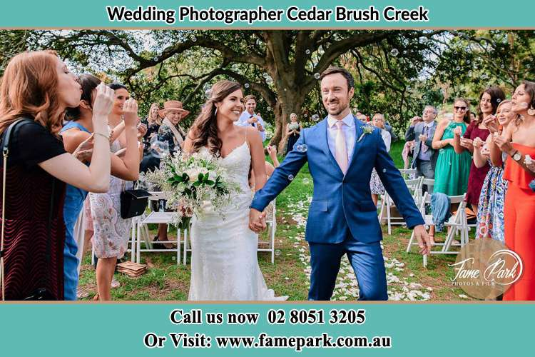 Photo of the Bride and the Groom showering bubbles by the visitors Cedar Brush Creek NSW 2259