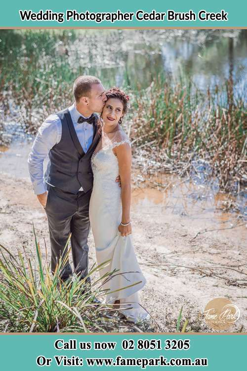 The Groom kissed her Bride near the lake Cedar Brush Creek