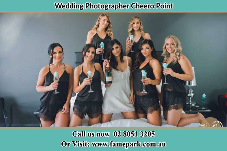 The bride holding a bottle of wine poses with the girls in front of camera Cheero Point