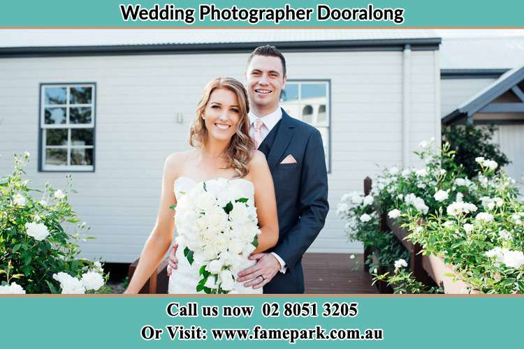 The Bride and the Groom smiling on the camera at the front of the house Dooralong NSW 2259