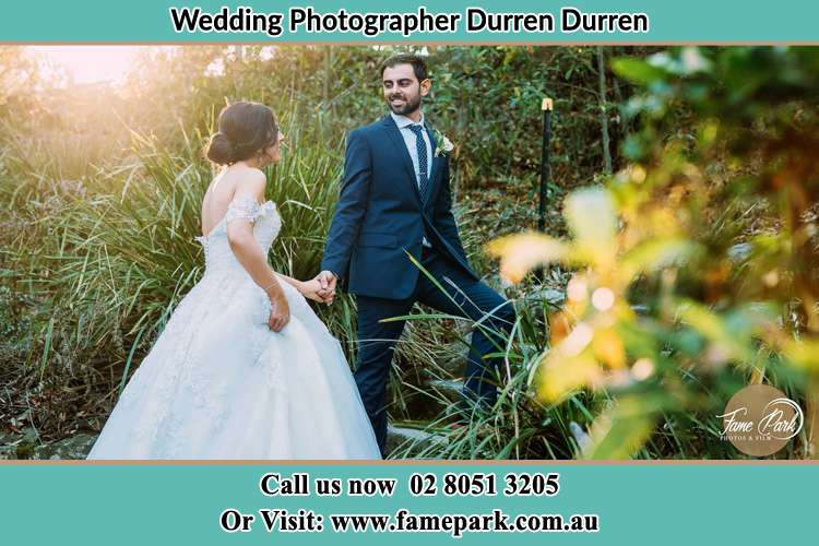 The Groom and the Bride hold their hands while looking at each other in the garden Durren Durren