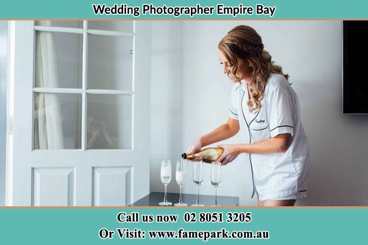 Photo of the Bride pouring wine the glasses Empire Bay NSW 2257