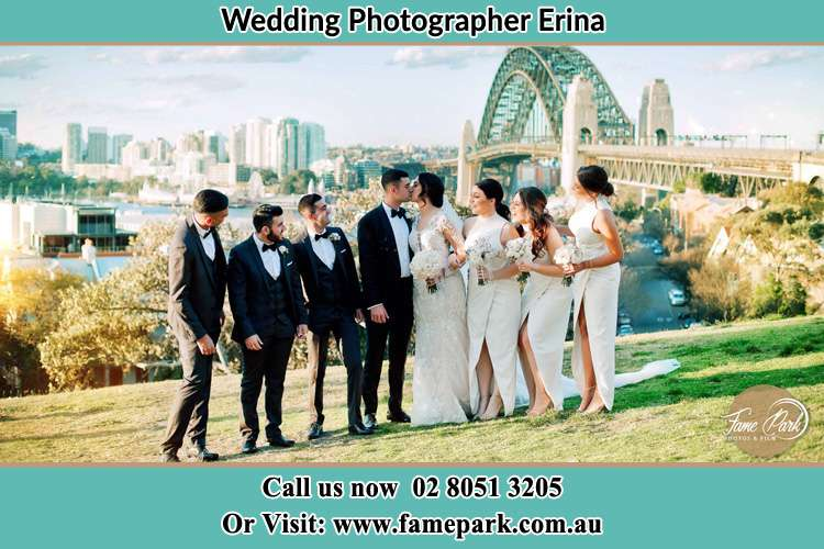 Photo of the Groom and the Bride kissing near the bridge while being watched by their entourage Erina