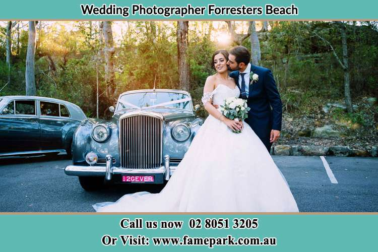 Photo of the Bride and Groom besides the bridal car Forresters Beach