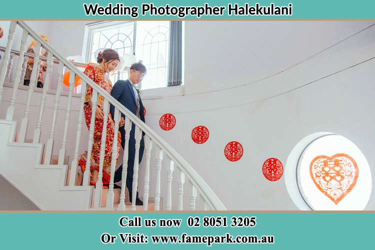 Photo of the Bride and the Groom walking down the stairs Halekulani