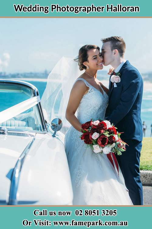 The Groom kissing his Bride besides their bridal car Halloran