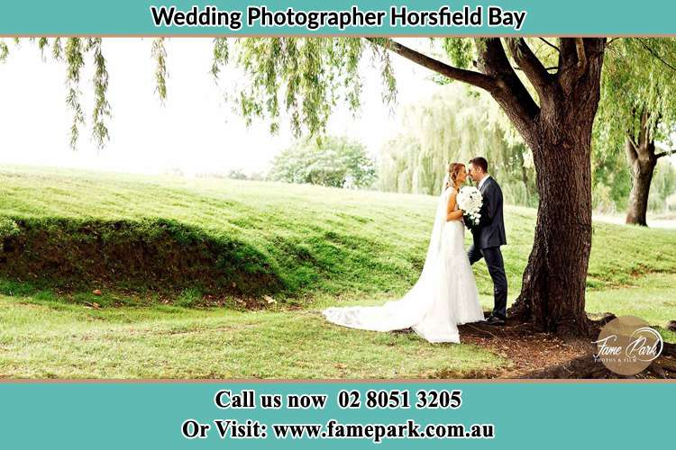 Photo of the Bride and the Groom kissing under the tree Horsfield Bay NSW 2256