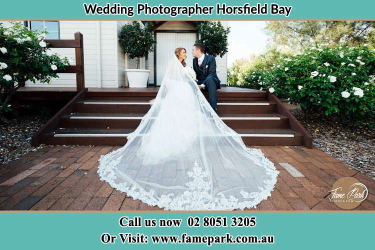 Photo of the Bride and the Groom looking each other while sitting at the staircase Horsfield Bay NSW 2256