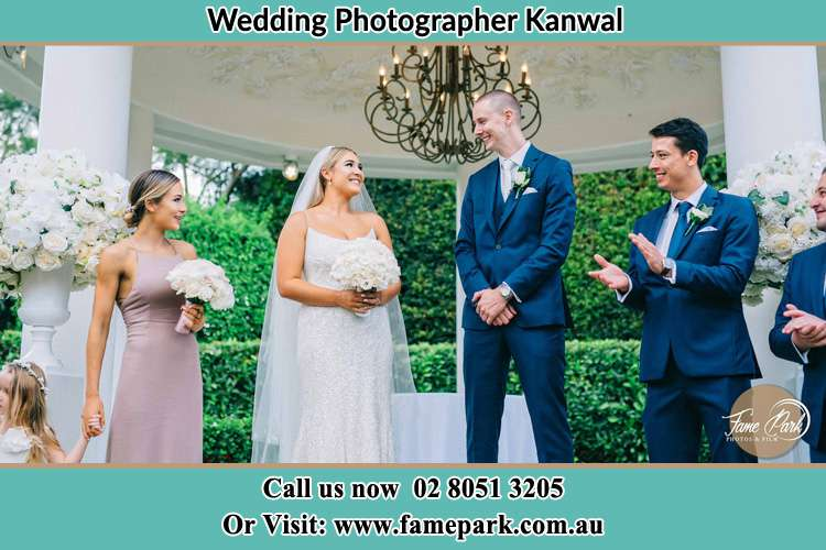 Photo of the Bride and the Groom happily looking each other with the entourage Kanwal NSW 2259