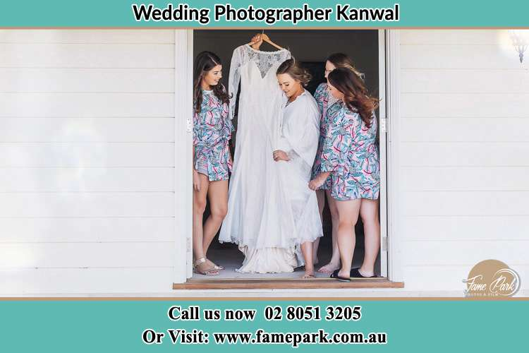 Photo of the Bride and the bridesmaids checking the wedding gown at the door Kanwal NSW 2259