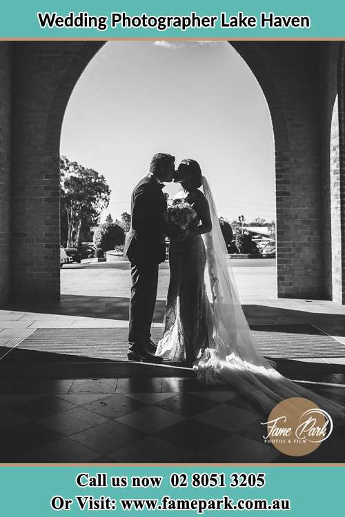 Photo of the Groom and the Bride kissing at the front of the church Lake Haven NSW 2263