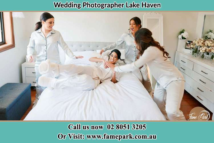 Photo of the Bride and the bridesmaids playing on bed Lake Haven NSW 2263