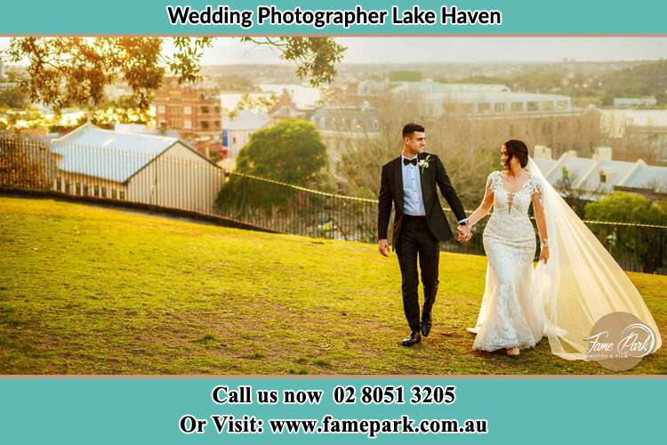 Photo of the Groom and the Bride holding hands while walking at the yard Lake Haven NSW 2263