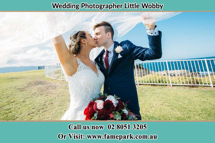 Photo of the Bride and the Groom kissing at the yard Little Wobby NSW 2256