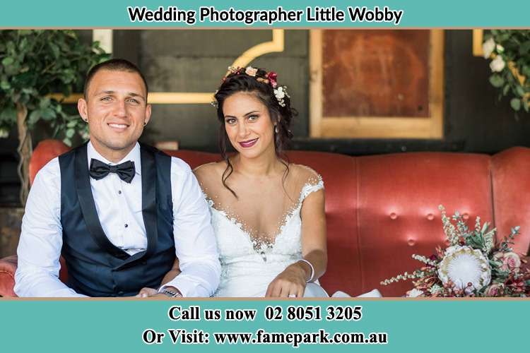 Photo of the Groom and the Bride sitting and smiling on the camera Little Wobby NSW 2256