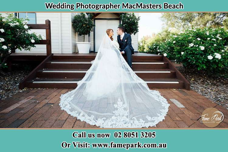 Photo of the Bride and the Groom looking each other while sitting at the staircase MacMasters Beach NSW 2251