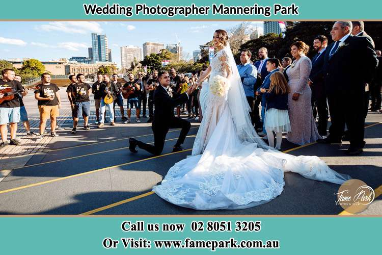 Groom Kneeling down in front of the Bride Mannering Park NSW 2250