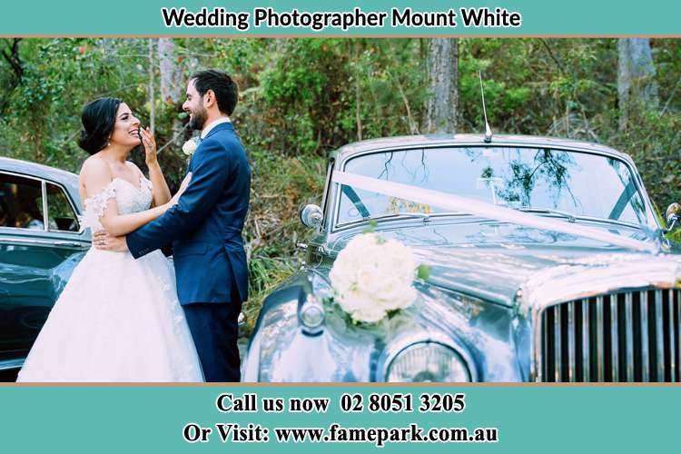 Photo of the Bride and the Groom besides the bridal car Mount White NSW 2250