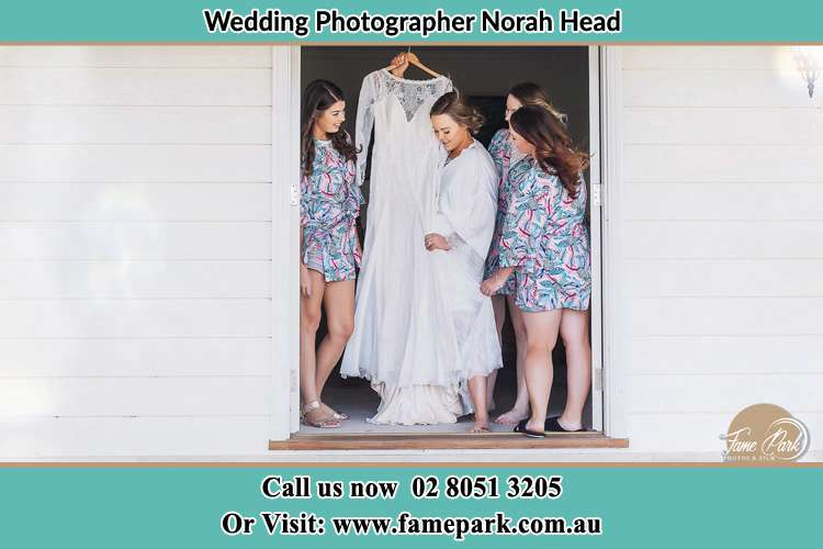 Photo of the Bride and the bridesmaids checking the wedding gown at the door Norah Head NSW 2263