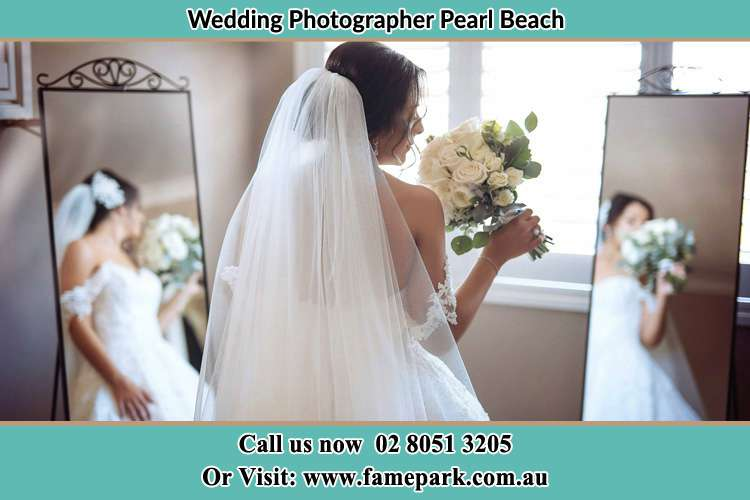 Photo of the Bride holding flower at the front of the mirrors Pearl Beach NSW 2256