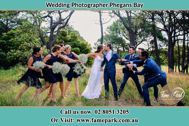 Photo of the Bride and the Groom kissing while teasing by the entourage Phegans Bay NSW 2256