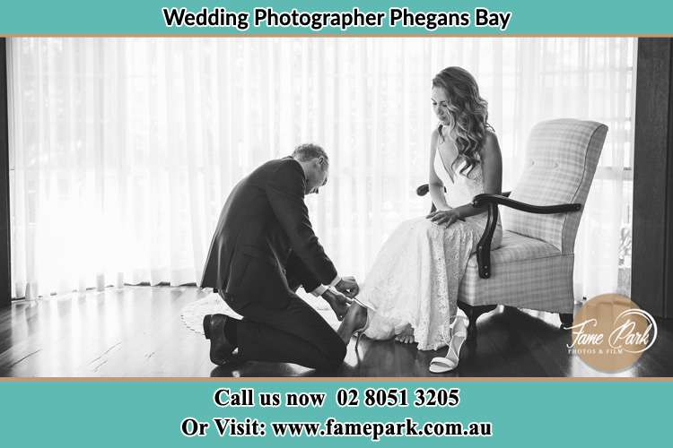 The Bride is being helped by the Groom trying to put on her shoes Phegans Bay NSW 2256