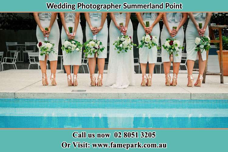 Behind photo of the Bride and the bridesmaids holding flower near the pool Summerland Point NSW 2259