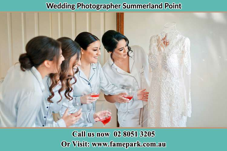 Photo of the Bride and the bridesmaids looking at the wedding gown Summerland Point NSW 2259