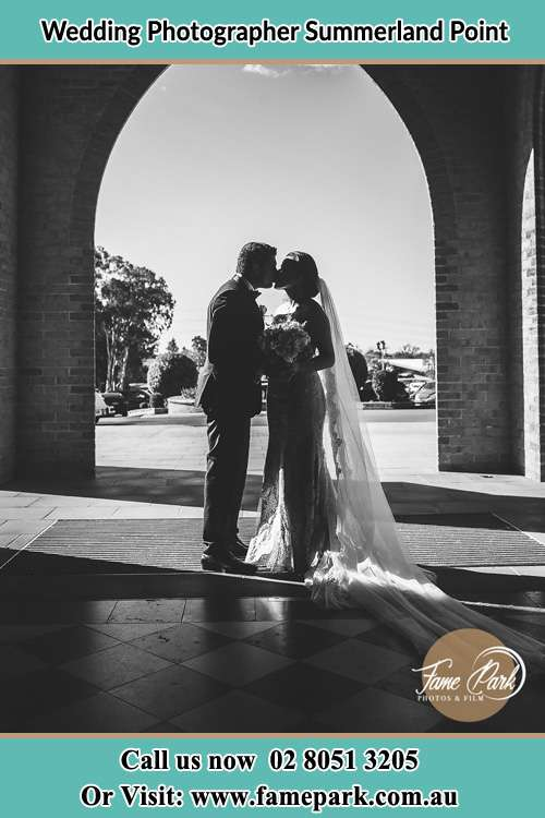 Photo of the Groom and the Bride kissing at the front of the church Summerland Point NSW 2259