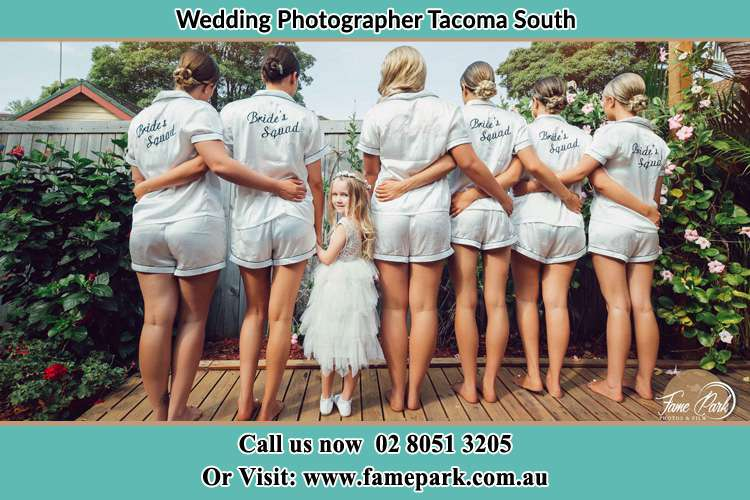 Behind photo of the Bride and the bridesmaids with the flower girl looking back Tacoma South NSW 2259