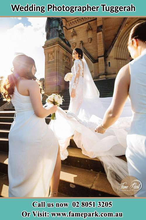 Photo of the Bride smiling at her bridesmaid holding the tail of her wedding gown at the front of the church Tuggerah NSW 2259