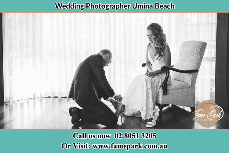 The Bride is being helped by the Groom trying to put on her shoes Umina Beach NSW 2257
