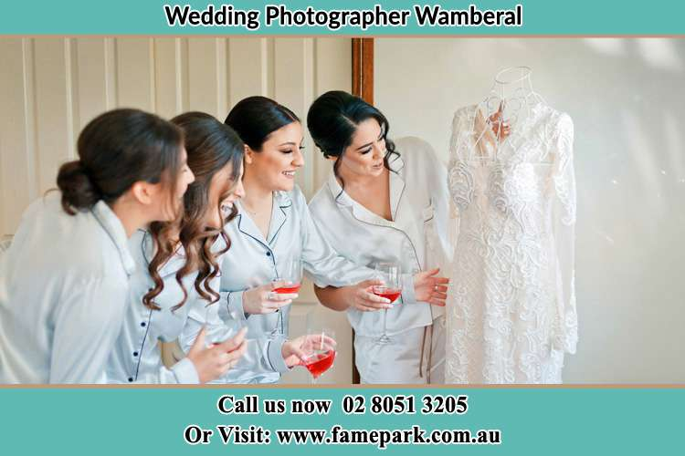 Photo of the Bride and the bridesmaids looking at the wedding gown Wamberal NSW 2260