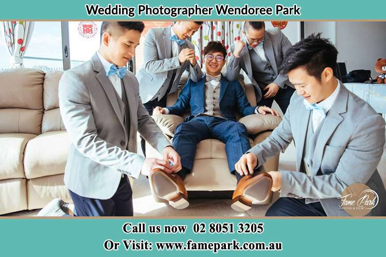 Photo of the Groom helping by the groomsmen getting ready Wendoree Park NSW 2250
