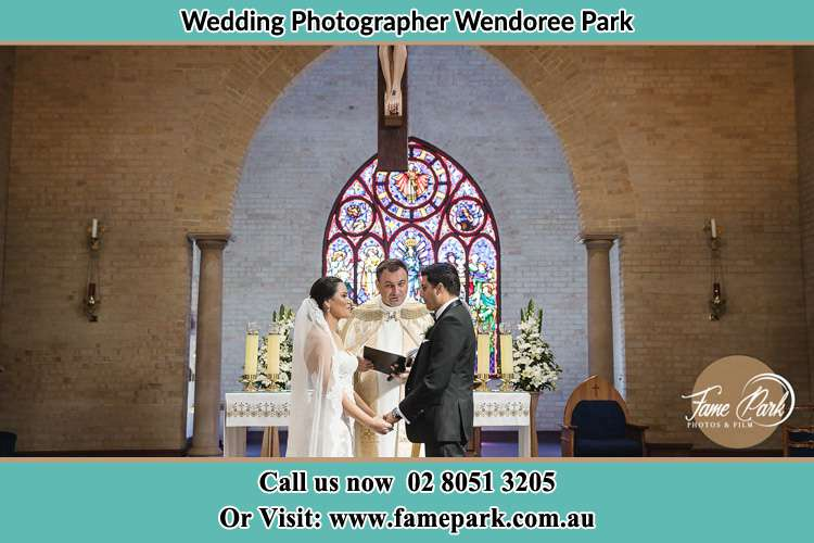 Photo of the Bride and the Groom with the Priest at the altar Wendoree Park NSW 2250