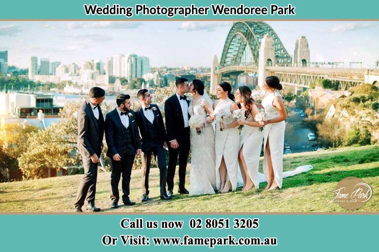Photo of the Groom and the Bride kissing with the entourage near the bridge Wendoree Park NSW 2250