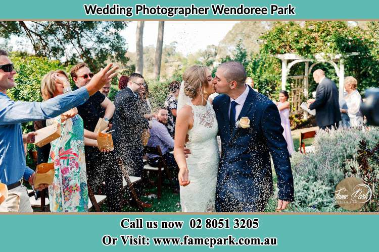 Photo of the Bride and the Groom kissing while showering rice by the visitors Wendoree Park NSW 2250